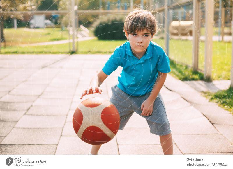 Ein fokussierter, süßer Athlet führt den Ball in einem Basketballspiel an. Ein Junge spielt nach der Schule Basketball. Sport, gesunde Lebensweise Dribbling