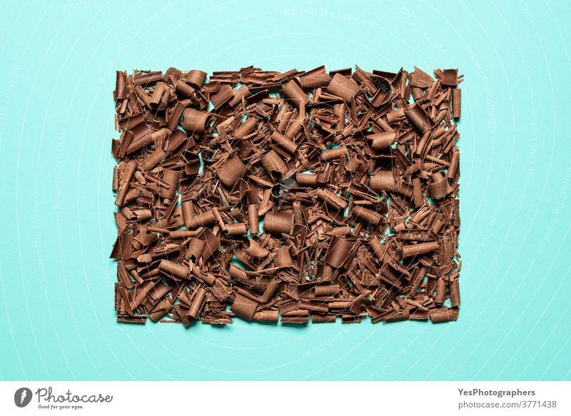 Schokoladenstücke auf blauem Hintergrund isoliert gestapelt. Draufsicht auf gehackte Schokolade backen bitter braun Schokoladenraspeln Weihnachten Stücke
