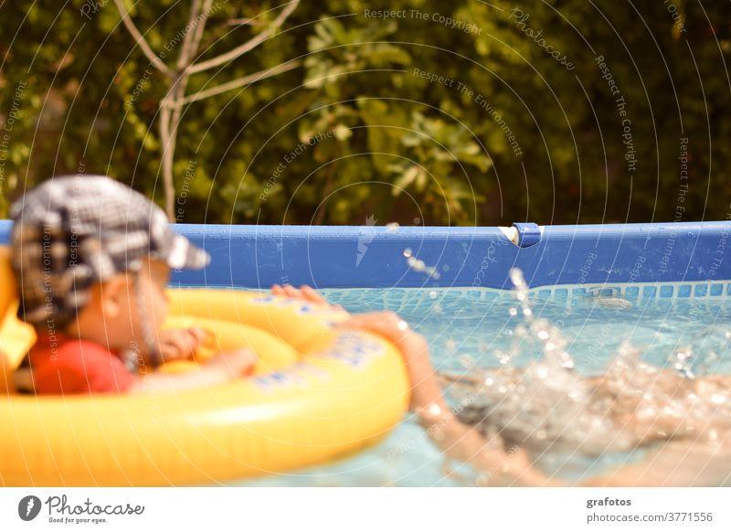 Surprise Kind Baden Pool Schwimmen Wald Überraschung gelb Kinderschwimmen Schwimmring Schwimmbad Sonne Sommer blau Spritzer Erschrecken