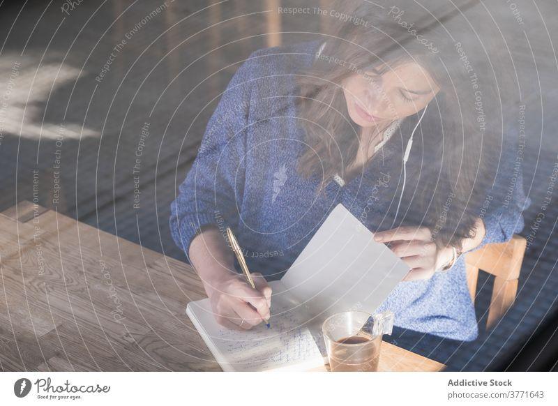 Nachdenkliche Frau macht sich Notizen in einem Notizbuch im Café zur Kenntnis nehmen nachdenklich Morgen gemütlich Notizblock Planer schreiben Kaffee Tasse