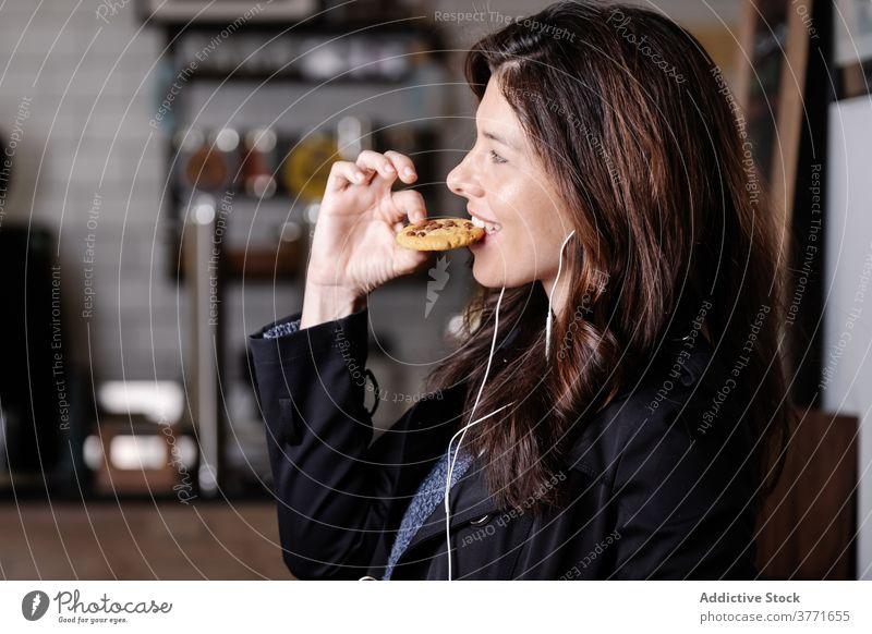 Erfreute Frau hört Musik im Café zuhören sorgenfrei genießen essen Keks Smartphone Kopfhörer lecker Lebensmittel Wochenende Apparatur Glück Vergnügen Dessert