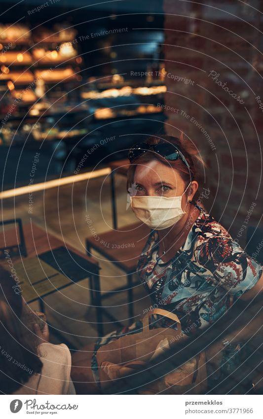 Junge Frau sitzt im Café an der Ladenfront im Stadtzentrum und trägt die Gesichtsmaske, um eine Virusinfektion zu vermeiden Kaukasier Gespräch covid-19