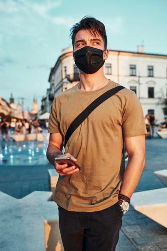 Junger Mann steht im Stadtzentrum und trägt die Gesichtsmaske, um eine Virusinfektion zu vermeiden Kaukasier Gespräch covid-19 Lifestyle Mundschutz Ausbruch