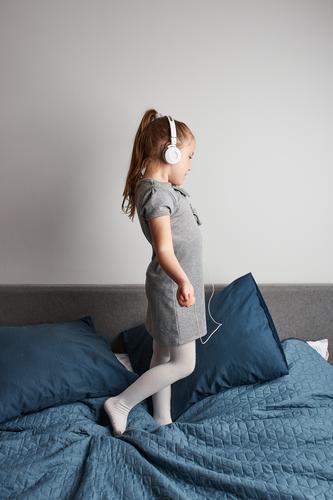 Kleines Mädchen singt tanzend und imitiert sich selbst als echte Sängerin Kind springend Spielen Gesang hören spielen singen Spaß Glück heimwärts Bett Kindheit