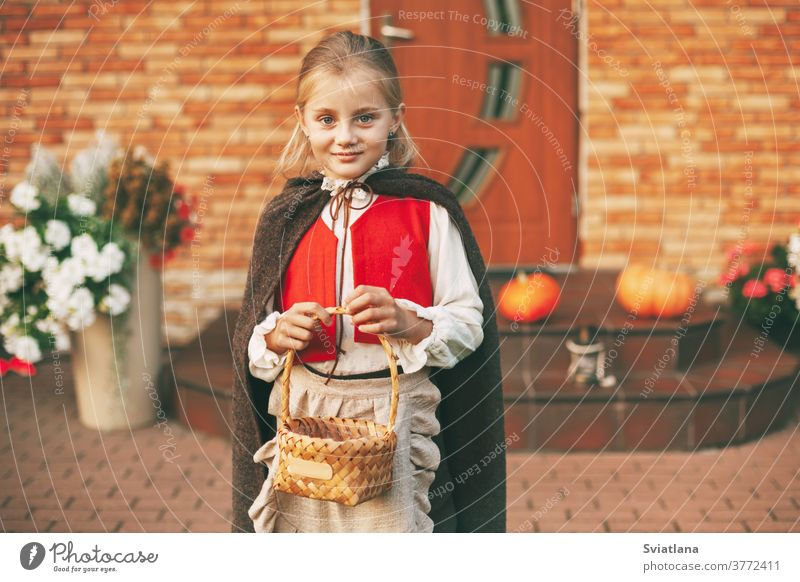 Ein kleines Mädchen in einem Feenkostüm mit einem Korb in der Hand während der Halloween-Feierlichkeiten kommt zu Besuch und holt sich Leckereien zu Hause