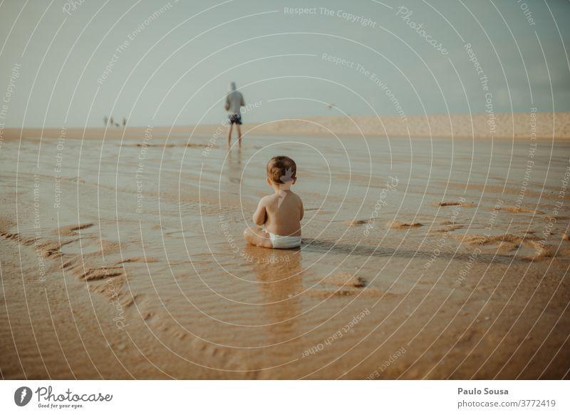 Rückansicht eines am Strand spielenden Kindes Kleinkind Kindheit Badeurlaub Sand Sandstrand Küste Natur Spielen Farbfoto Sommerurlaub Erholung Außenaufnahme