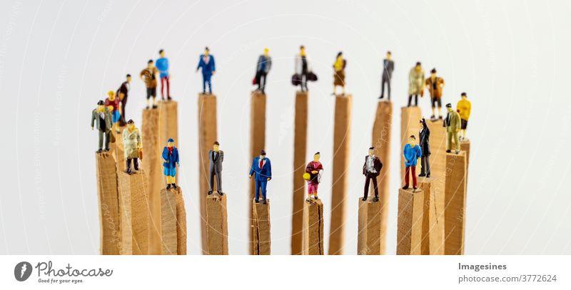 Soziale Distanzierung. Ein Kreis von Miniatur Spielzeug Menschen auf Holzpfählen die Abstand halten Soziale probleme Covid-19 Teamwork Konzepte Reduzierung