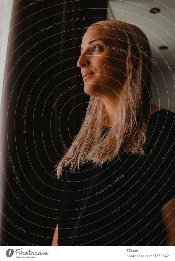 Junge Frau sieht aus dem Fenster junge frau blond lange haare schwarz vorhang portrait gesicht sportlich blick tageslicht Gesicht natürlich junge Frau Schönheit