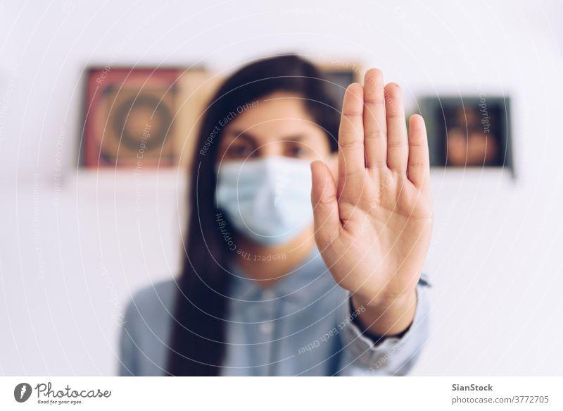 Coronavirus-Konzept. Mädchen, die zum Schutz eine Maske tragen, sagen, dass sie mit ihren Händen dem Coronavirus Einhalt gebieten sollen. Weltweiter Aufruf, zu Hause zu bleiben.