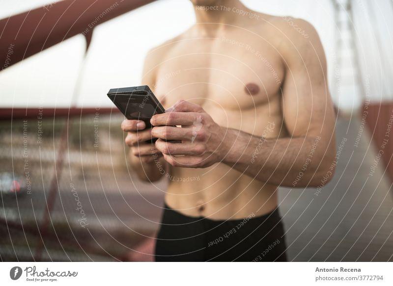 Training der Läufer ohne Hemd auf der roten Brücke und Blick auf die Telefonstatistik laufen Mann stark passen Fitness Steg Fußweg Männer männlich