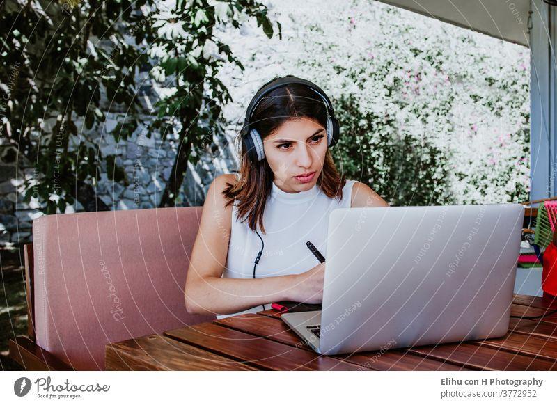 junge Lateinamerikanerin sitzt allein im Heimbüro, arbeitet am Laptop und hört Musik über Kopfhörer, mexikanisches Mädchen in Mexiko arbeitet zu Hause Drahtlos