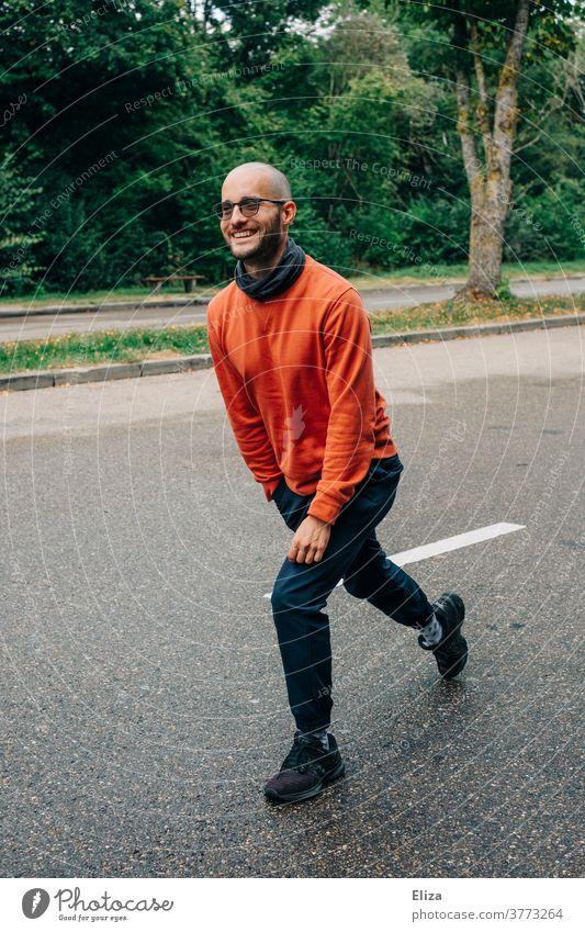 Ein Mann macht Lunges (Ausfallschritte) auf einer Raststätte um sich in der Pause einer Autofahrt etwas zu bewegen Bewegung draußen zwischendurch Straße lächeln