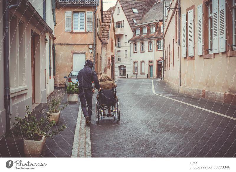 Ein Mann schiebt eine Person mit Behinderung im Rollstuhl die Straße entlang Mobilität Handicap Gesundheitswesen Pflege Regenwetter Krankheit Ausflug schieben