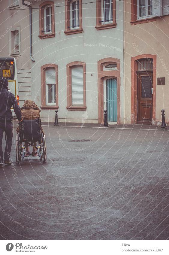 Ein Mann schiebt eine Person mit Behinderung im Rollstuhl Mobilität Handicap Gesundheitswesen Pflege Regenwetter Krankheit Ausflug schieben Gehbehinderung