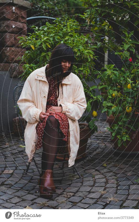 Dunkelhaarige Frau in herbstlicher Kleidung sitzt draußen im Hof auf einem Stuhl und blickt zur Seite dunkelhaarig Herbst langhaarig Blick zur Seite verträumt