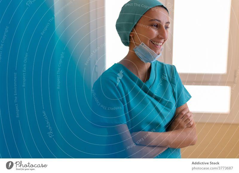 Fröhliche Krankenschwester ruht in der Nähe von Fenster im Krankenhaus Krankenpfleger Sanitäter Frau Glück heiter Klinik Arbeit medizinisch Lächeln positiv