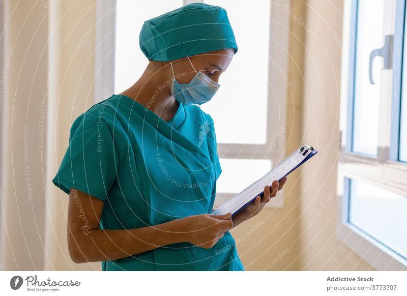 Krankenschwester schreibt auf Klemmbrett im Krankenhaus Krankenpfleger schreiben zur Kenntnis nehmen Sanitäter Frau Klinik Zwischenablage Arbeit medizinisch