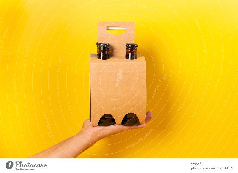 Hand hält eine Bierpräsentation im Viererpack mit gelbem Hintergrund bayerisch Belgier Getränk Schnaps Flasche Flaschen Kasten Marke Markenbildung Brauerei