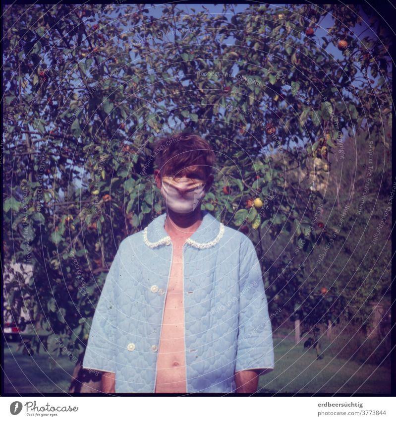 Verkaterter Mann mit Katzenmaske und Morgenmantel (im Grünen vor Apfelbaum) Maske Mundnasenschutz Haare Frisur zerzaust Kater verkatert Bauch bauchfrei grün