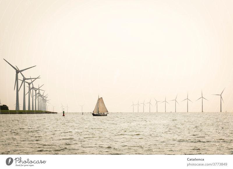 Ein Plattbodenschiff vor einem Windpark im IJsselmeer Erneuerbare Energie Windräder Natur Wasser Wellen windig Schifffahrt Meer Segelyacht Horizont Wolken