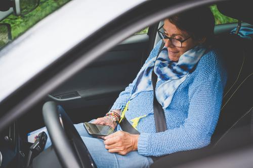 Eine Frau sitzt im Auto auf dem Beifahrersitz und sieht auf ihr Smartphone Handy sitzen benutzend beschäftigt Lächeln Telefon mobiltelefon Technik & Technologie