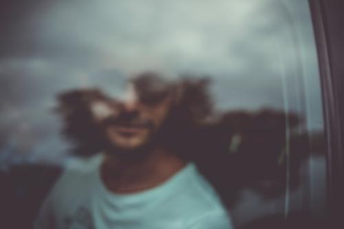 Ein Mann guckt aus dem Fenster eines Autos. Verschwommen. Verkehr Scheibe rausgucken verschwommen unscharf Unschärfe Wolken Spiegelung Glasscheibe