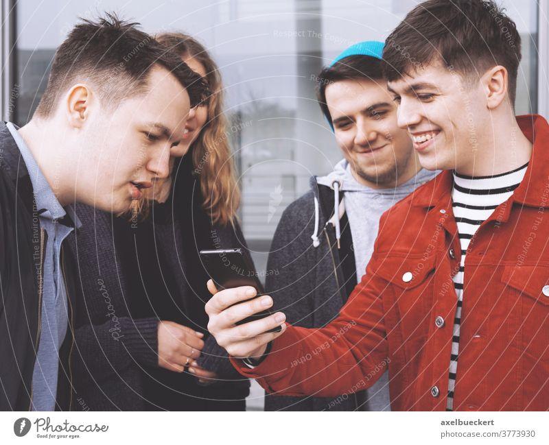 junger Mann, der einer Gruppe von Freunden etwas Lustiges auf dem Smartphone zeigt Teenager Menschengruppe echte Menschen Lifestyle zeigen Handy lustig zusammen