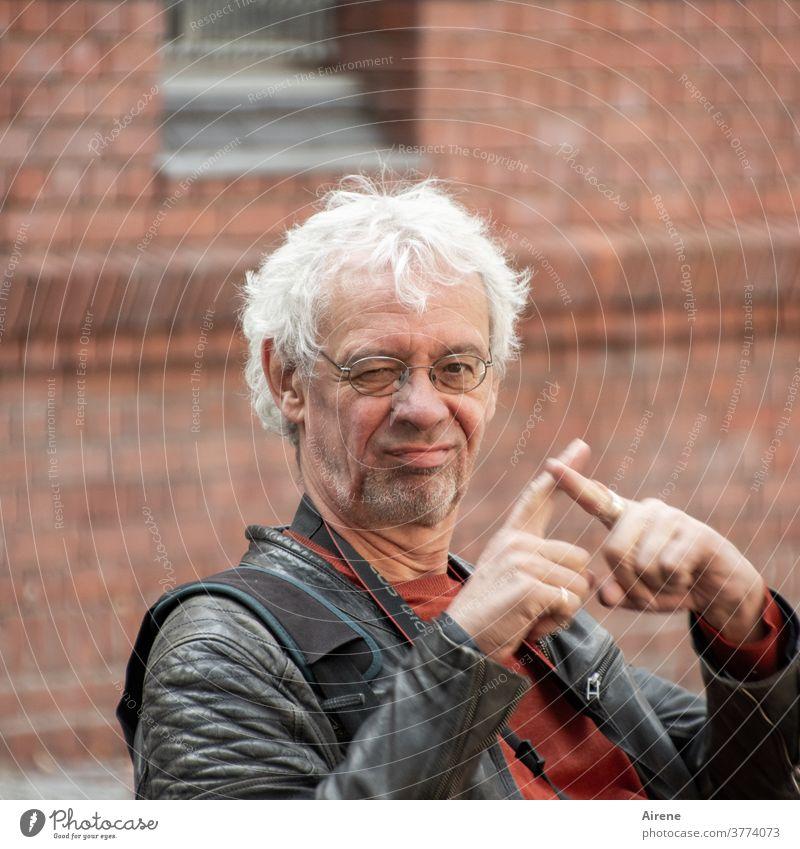 Was wollen diese Hände uns sagen? Porträt skeptisch freundlich lächeln kritisch ironisch Humor Kritik Zeichen Geste Finger Hand kreuzen weißhaarig Brille