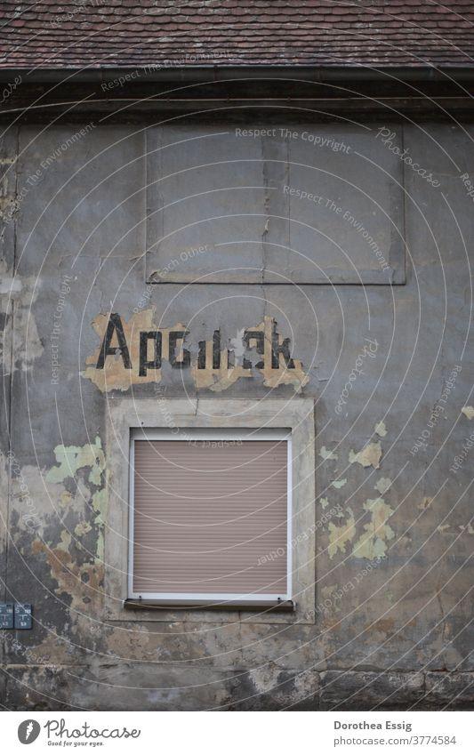 "Verblasster Schriftzug - ""Apotheke"" an Hauswand Verfall Gebäude alt kaputt Mauer Fassade Fenster Vergänglichkeit Farbfoto Gedeckte Farben Außenaufnahme grau"