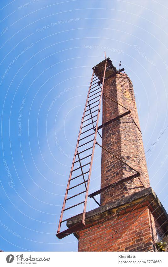 Alter Fabrikkamin aus roten Ziegelsteinen mit verrosteter Steigleiter ragt in den blauweisen Himmel- Lost Place alt roter Ziegelstein Architektur Außenaufnahme