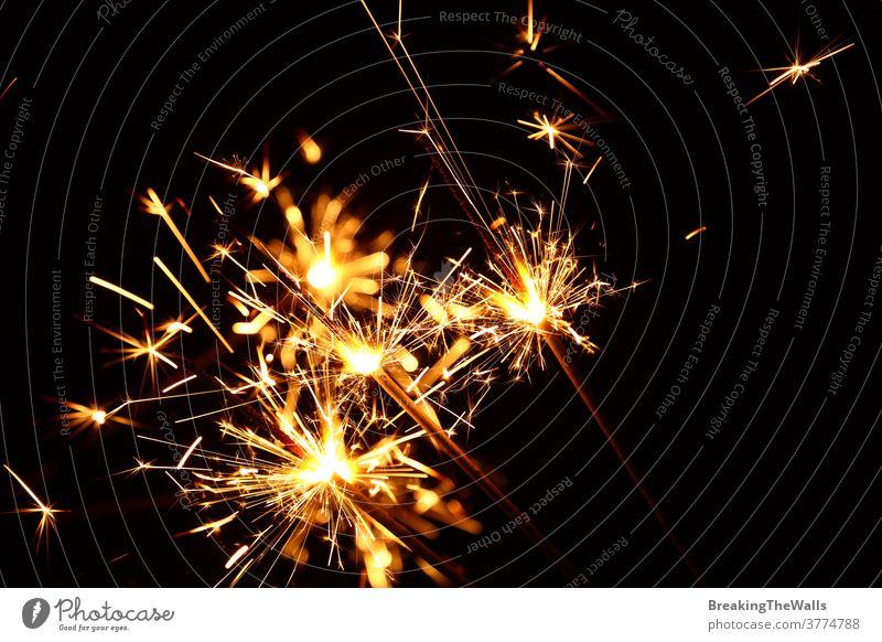 Nahaufnahme mehrerer Feuerwerkskerzen über Schwarz Wunderkerze Funken funkeln Menschengruppe dunkel schwarz Hintergrund schließen nach oben tiefstehend Winkel