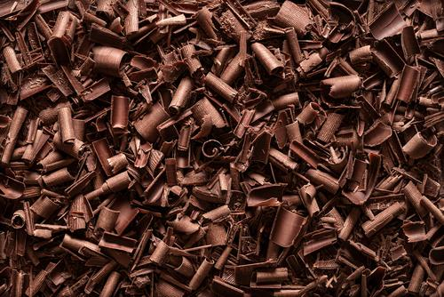 Schokoladenstücke im Hintergrund. Draufsicht auf Schokoladenspäne obere Ansicht backen bitter schwarz braun Schokoladenraspeln gehackt Weihnachten Stücke