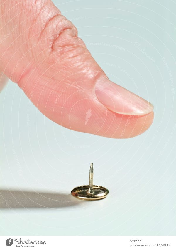 Nahaufnahme eines Daumens über einer Reißzwecke Reisszwecke Reissnagel Finger Gefahr Verletzung verletzungsgefahr Mensch Fingernagel Makroaufnahme Nagel Risiko