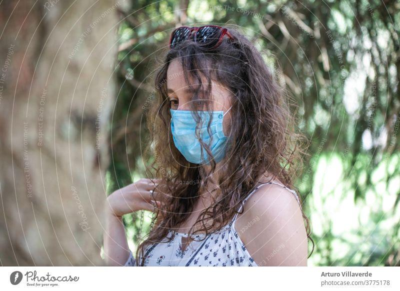 Porträt eines jungen Mädchens mit einer Maske, das zwischen Bäumen spazieren geht Quarantäne Garten im Freien Gesundheit covid-19 Coronavirus Park Virus Seuche