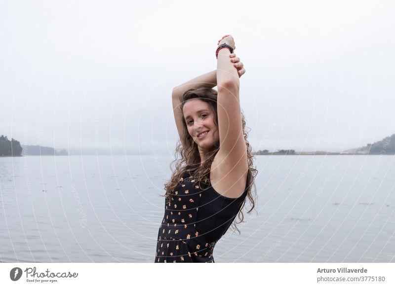junges Mädchen posiert mit erhobenen Armen mit dem Meer im Hintergrund an einem bewölkten Tag Frauen MEER wolkig Spanien Schönheit Mode Strand Wasser Himmel