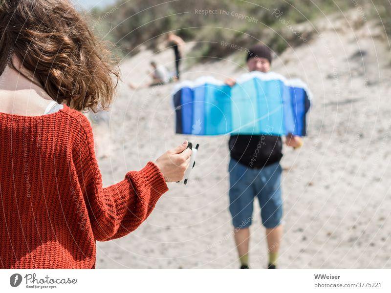 Drachen steigen lassen erfordert eine gute Abstimmung zwischen Vater und Tochter Wind Strand Sonne Flugmatte Lenkmatte Lenkdrachen Mädchen Kind Locken Haare