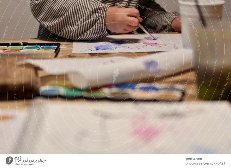 Ein Kind sitzt am Tisch und malt mit Wasserfarben, Kreativität pinsel mallen malkasten wasser kreativ kindheit Freizeit & Hobby mehrfarbig