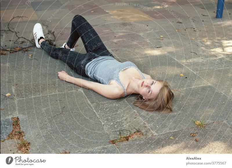 Portrait einer jungen Frau, die auf dem Boden liegt und nach hinten oben in die Kamera schaut junge Frau schlank schön athletisch blond 18-25 Jahre rotblond