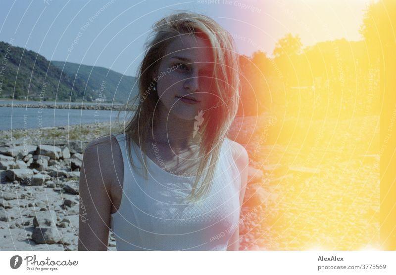 Gegenlicht- Portrait einer jungen Frau am Rheinufer, die auf einem Steindamm steht - mit Lichterscheinung oder Belichtungsfehler und Lightleaks junge Frau