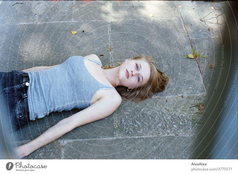 Portrait einer jungen Frau, die auf dem Boden liegt und nach oben durch Gitter in die Kamera schaut junge Frau schlank schön athletisch blond 18-25 Jahre