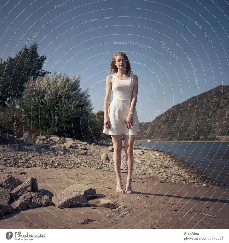 Analoges Portrait einer jungen, barfüßigen Frau am Rheinufer, die am Rheinufer steht junge Frau schlank schön athletisch blond rotblond Haare schauen sehen