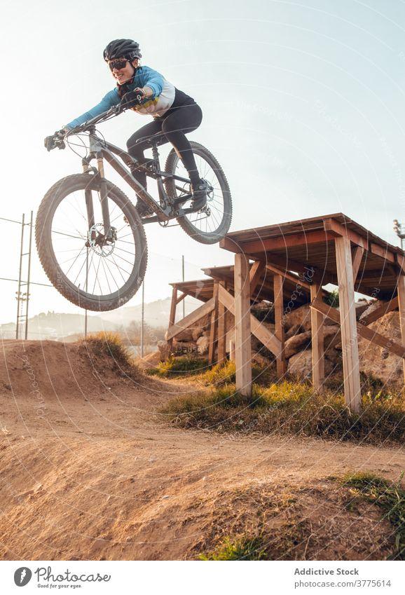 Radfahrerin mit Helm beim Üben auf der Trainingsstrecke Bahn Berge u. Gebirge Fahrrad praktizieren Frau Schutzhelm Testversion Trick Sportlerin Sportbekleidung