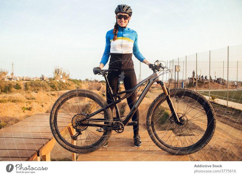Sportliche junge Frau in Helm mit Fahrrad schaut in die Kamera Schutzhelm Lächeln Berge u. Gebirge Testversion Radfahrer Trick Sportlerin Radfahren