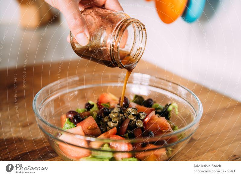 Nahaufnahme von Frauenhänden, die Dressing über einen Salat gießen. Salatbeilage Gemüse Essig balsamisch eingießen frisch Gewürz Gesundheit natürlich