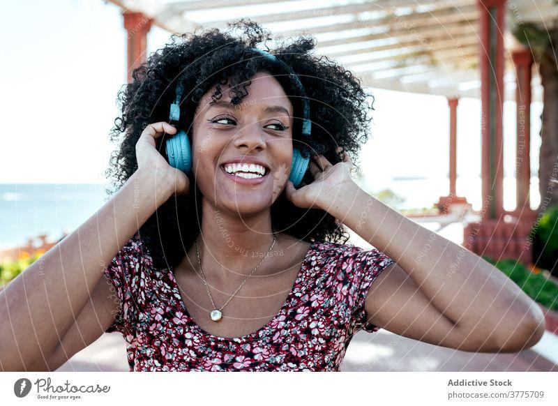 Lächelnde schwarze Frau genießt Musik auf der Promenade Drahtlos Kopfhörer zuhören genießen Freude sorgenfrei Sommer Spazierweg ethnisch Afroamerikaner