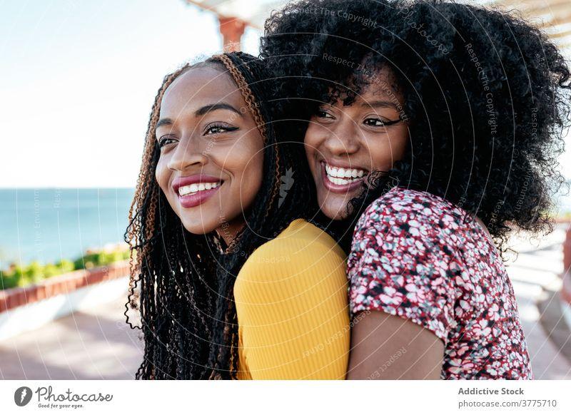 Fröhliche ethnische Frauen, die sich an der Strandpromenade umarmen bester Freund Umarmung Freundschaft Zusammensein Freude Sommer Stauanlage schwarz