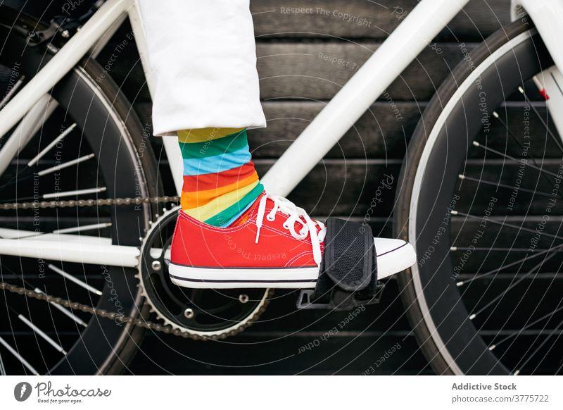 Crop Person in bunten Socken auf dem Fahrrad Streifen Kniestrümpfe farbenfroh Regenbogen kreativ Spaß Fahrzeug modern Großstadt Straße urban Stil trendy Verkehr