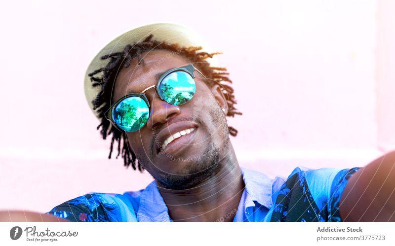 Lächelnder schwarzer Mann nimmt Selfie in der Stadt Smartphone tropisch Hemd drucken Stil trendy Freude benutzend männlich ethnisch Afroamerikaner Gebäude