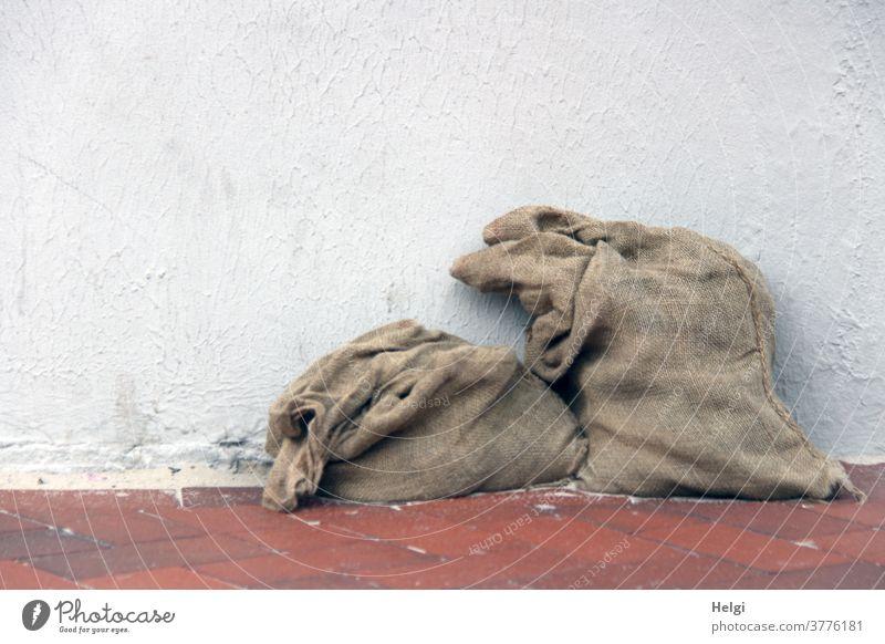 AST ;-) - zwei alte zum Teil gefüllte Jutesäcke auf rotem Klinkerboden lehnen an einer weißen Wand Sack Jutesack 2 stehen braun grau Farbfoto Menschenleer
