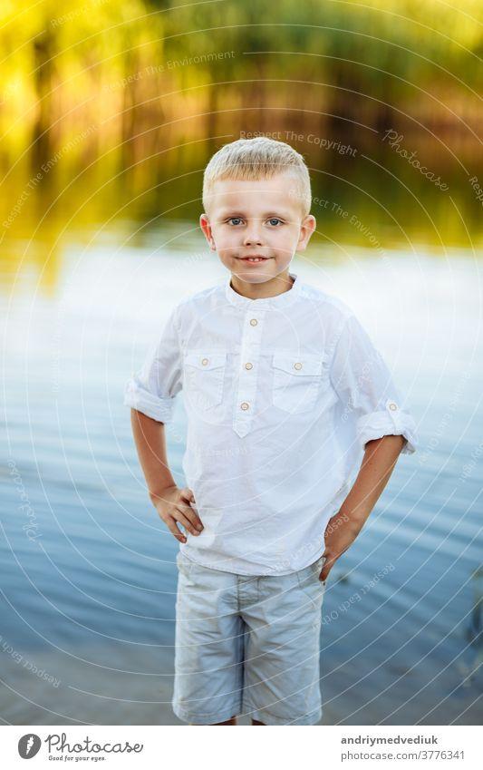 Porträt eines glücklichen und schönen kleinen Jungen mit blonden Haaren und weißem Hemd, Glückliche Kindheit. Positive Emotion. Porträt in der Nähe des Flusses in der Natur